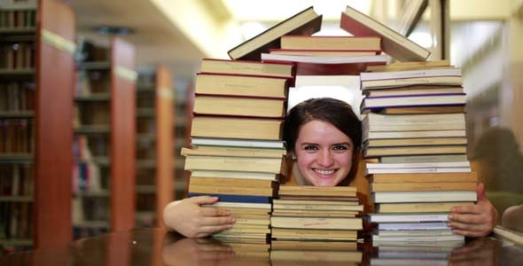 Student Gazing Through House-Shaped Stack Of Books