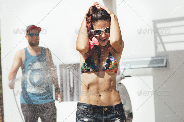 Man pouring water from a hose girl. - Stock Photo - Images