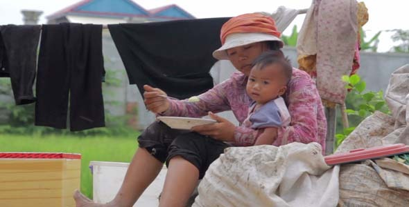 VideoHive Mother Sitting Top Of Garbage Bag Feeding Baby 7873356