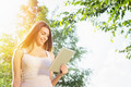 Pretty young woman with tablet in park on sunny summer day - PhotoDune Item for Sale
