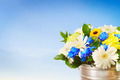 Bouquet of bright flowers in a bucket against blue sky - PhotoDune Item for Sale