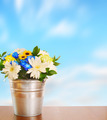 Bouquet of flowers in a metal bucket against blue sky - PhotoDune Item for Sale