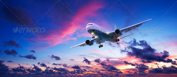 Jet aircraft cruising in a sunset sky - Stock Photo - Images