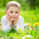 Smiling little boy lying in green grass - PhotoDune Item for Sale