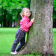 Portrait oflittle girl embracing tree in park - PhotoDune Item for Sale