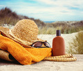 Straw hat with towel and lotion at the beach - PhotoDune Item for Sale