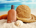 Straw hat with towel and lotion on the beach - PhotoDune Item for Sale