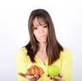 Doubtful woman holding an apple and croissant trying to decide w - PhotoDune Item for Sale