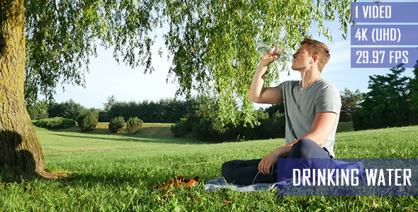 Healthy Man Drinks Water In The Park
