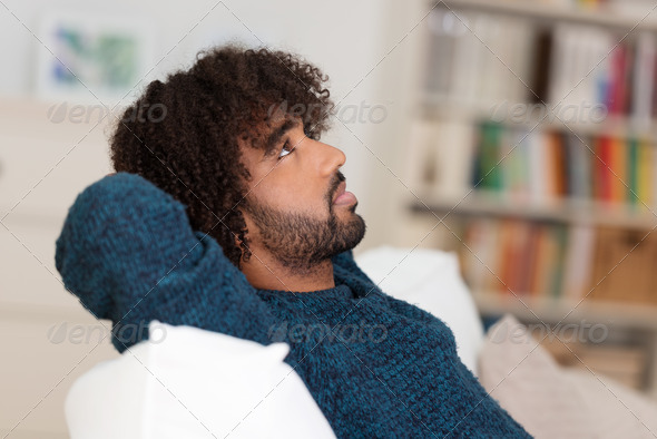 Young African American man sitting thinking - Stock Photo - Images