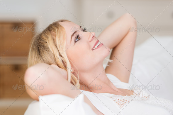 Pretty blond woman lying daydreaming - Stock Photo - Images