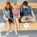 Three college students looking tablet top view - PhotoDune Item for Sale