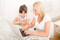 Mother and Daughter with a Laptop at home - PhotoDune Item for Sale