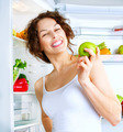 Diet. Beautiful young woman near the fridge with healthy Food - PhotoDune Item for Sale