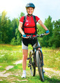 Happy young woman riding bicycle outside - PhotoDune Item for Sale