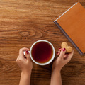 woman holding hot cup of tea with cookies - PhotoDune Item for Sale