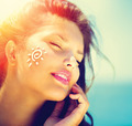 Beauty Girl Applying Sun Tan Cream on her Face. Sun Tanning - PhotoDune Item for Sale