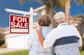 Happy Senior Couple Front of For Sale Real Estate Sign and House. - PhotoDune Item for Sale