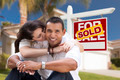 Young Happy Hispanic Young Couple in Front of Their New Home and Sold For Sale Real Estate Sign. - PhotoDune Item for Sale