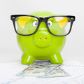 Green piggy bank over stock market chart with 100 dollars banknote - 1 to 1 ratio - PhotoDune Item for Sale