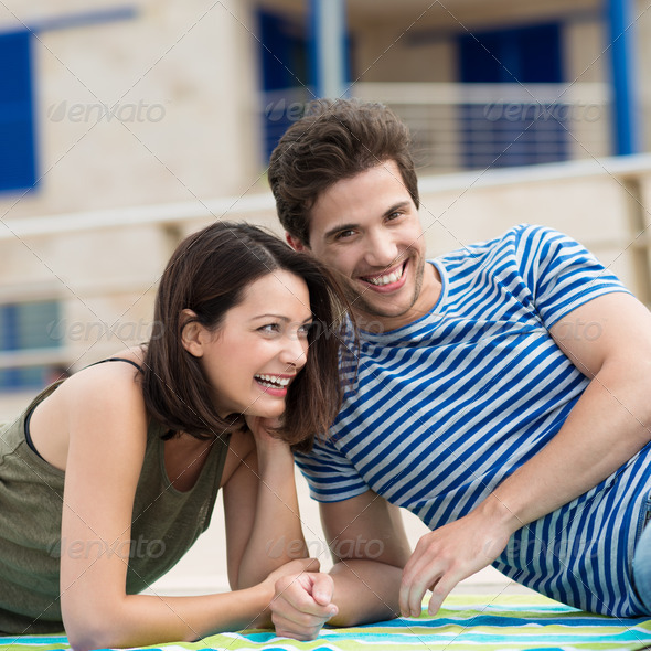 Laughing happy couple relaxing on a towel - Stock Photo - Images