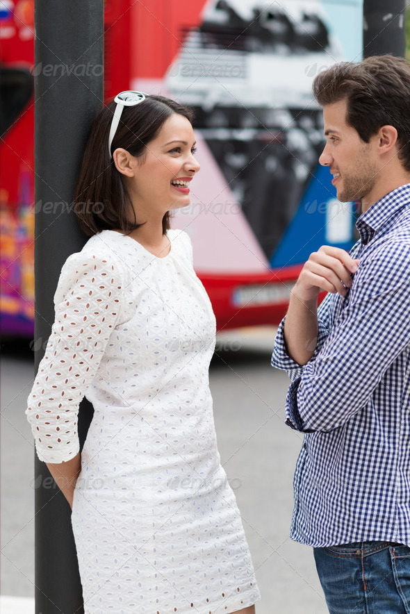 Stylish young couple standing talking in a street - Stock Photo - Images