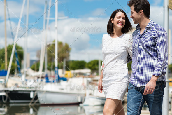 Young couple strolling past a small boat harbour - Stock Photo - Images