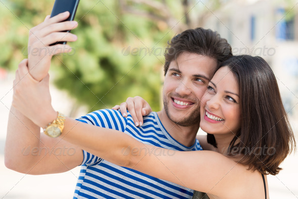 Vivacious couple taking a selfie on their mobile - Stock Photo - Images