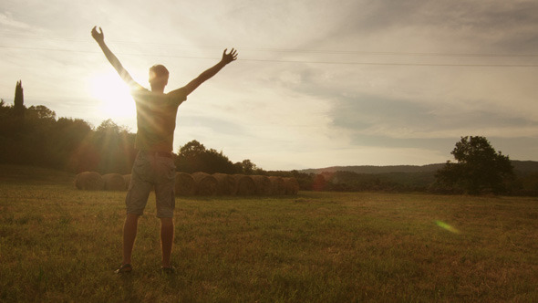 Young Man Walking And Raising Hands in the Field