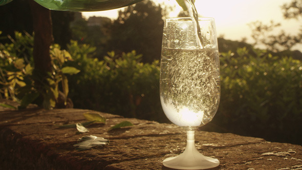 Pouring Water into Glass in Sunset Light