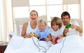 Loving family playing video game in the bedroom