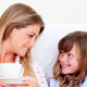 Download Attentive mother and her daughter drinking coffee lying in bed from PhotoDune