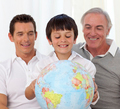 Son, father and grandfather looking at a terrestrial globe