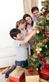 Happy family decorating a Christmas tree with boubles