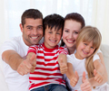 Family sitting on sofa with thumbs up