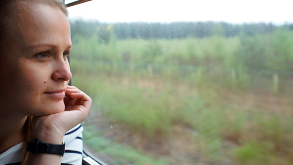Young Woman Looking Out The Window Of Moving Train