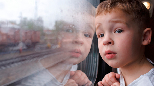Curious Boy Looking Out Of The Train Window