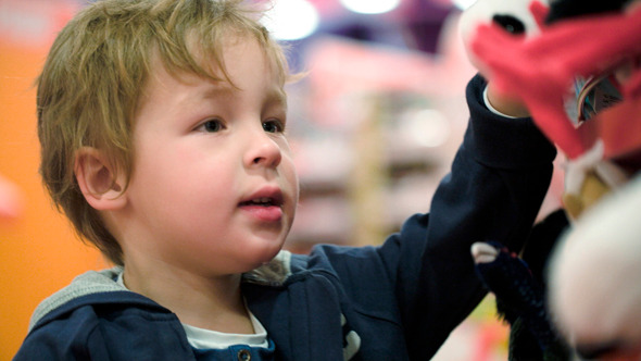 Little Child Choosing Soft Toys In The Shop