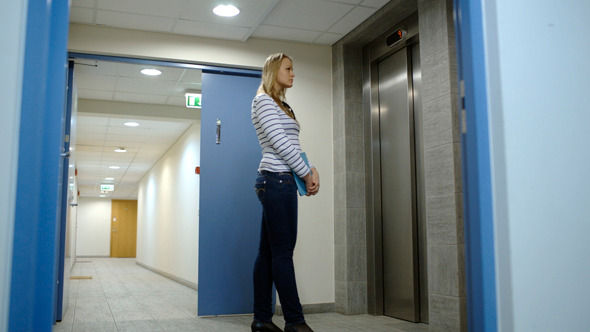 Young Woman Calling And Waiting For Elevator