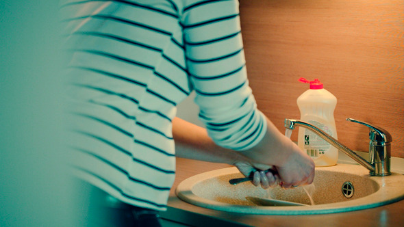Woman Washing The Dishes In The Kitchen At Home