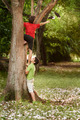 Two children helping and climbing on tree in park - PhotoDune Item for Sale
