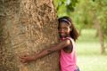 Portrait of black ecologist girl hugging tree and smiling - PhotoDune Item for Sale
