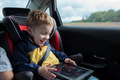 Happy boy playing with touchpad in the car - PhotoDune Item for Sale