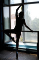 Ballet dancer exercising at the barre by the window - PhotoDune Item for Sale