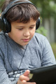Teenager in headphones using pad outdoor - PhotoDune Item for Sale