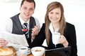Young couple of business people reading a newspaper while having