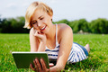 Smiling woman browsing the web on her tablet - PhotoDune Item for Sale