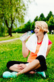 Woman runner sitting on the grass and drinking water - PhotoDune Item for Sale