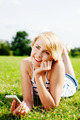 Young blond woman listening to mp3s in the park - PhotoDune Item for Sale
