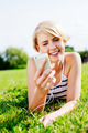 Pretty blonde listening to mp3s on her smartphone - PhotoDune Item for Sale